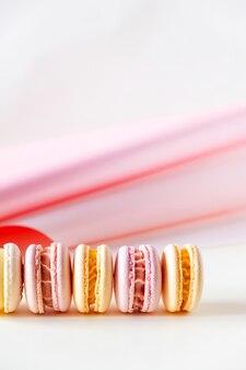 Rij van kleurrijke pastel franse macarons of macarons op witte en roze achtergrond