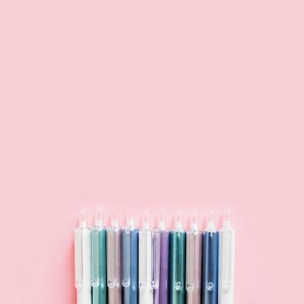 Rij van kleurrijke pennen op roze achtergrond