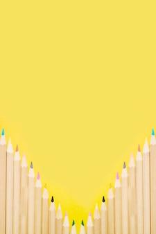 Rij van kleurrijke potloden op gele achtergrond
