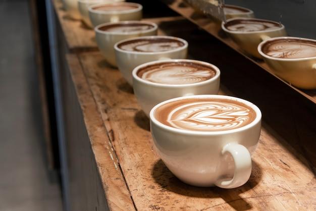 Rij van latte kunstkoffie op houten plank