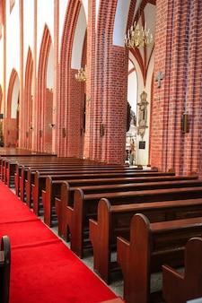 Rij van lege houten stoelen in het interieur van een middeleeuwse katholieke kathedraal. wroclaw, polen