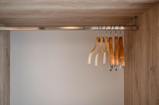 Rij van lege kleerhanger op rvs rail in houten kast