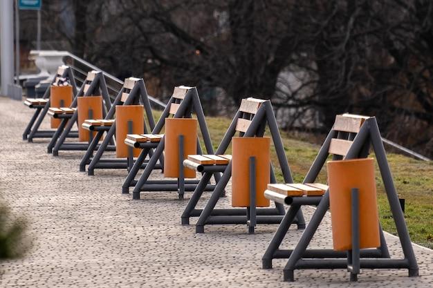 Rij van lege nieuwe houten banken en vuilnisbakken op een stoep in een stadspark.