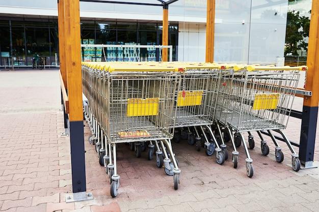 Rij van lege winkelwagen in de buurt van een winkel, close-up