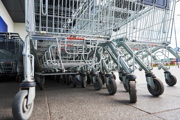 Rij van lege winkelwagen in de buurt van een winkel close-up