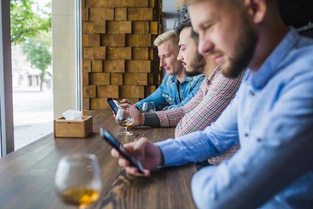 Rij van mannelijke vrienden met behulp van hun mobiele telefoons in het restaurant