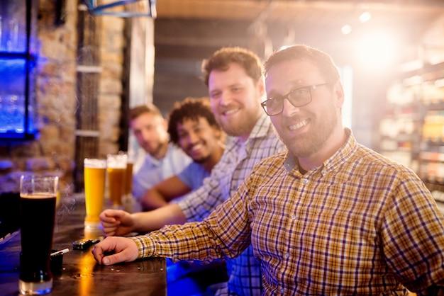 Rij van mannen zitten in de bar met licht en donker bier van de tap