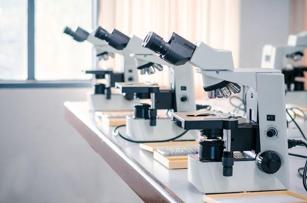 Rij van microscoop met microplaat op witte lijst in laboratorium die voor onderzoek en het leren plaatsen