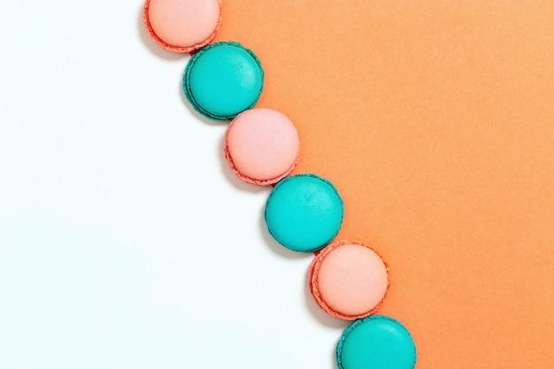 Rij van munt en roze macarons. bovenaanzicht. ruimte kopiëren. pastelkleuren.