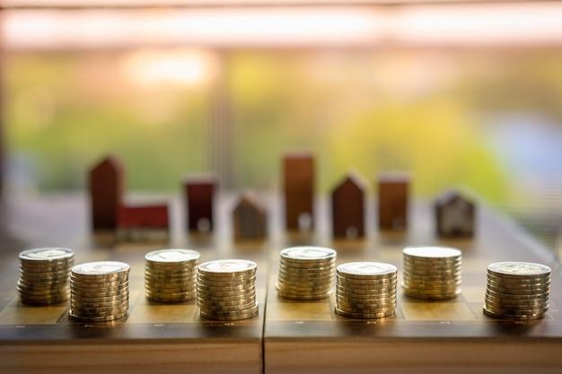Rij van muntgeld op schaak breed met modelachtergrond van het onduidelijk beeld de houten huis, de markt van onroerende goederen