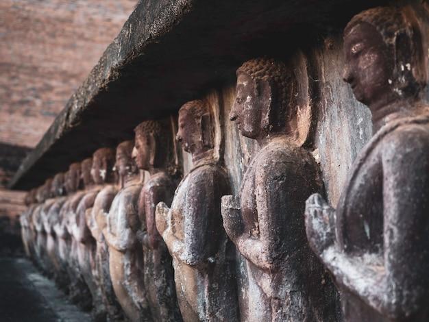 Rij van oud stucwerk, biddend boeddhabeeld aan de voet van de oude pagode in de wat mahathat-tempel in het district van sukhothai historical park, een unesco-werelderfgoed in thailand, close-up.