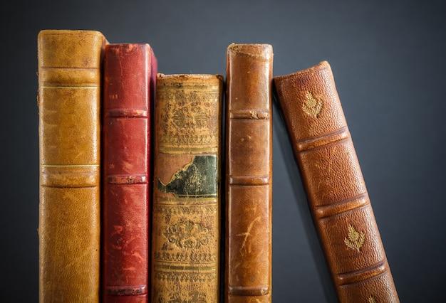 Rij van oude boeken geïsoleerd op donkere achtergrond