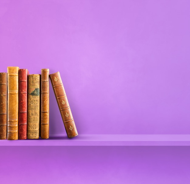 Rij van oude boeken op paarse plank. vierkante scène achtergrond
