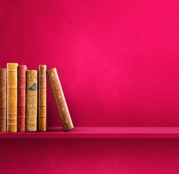 Rij van oude boeken op roze plank. vierkante scène achtergrond