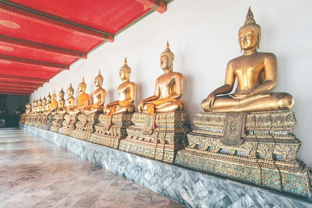 Rij van prachtige gouden boeddhabeeld in thailand. kunst van artistieke boeddha