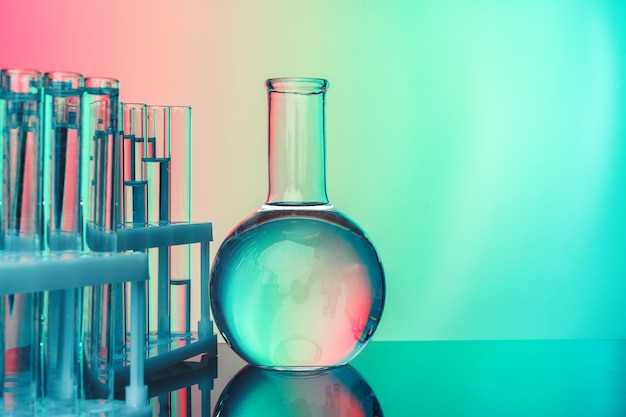 Rij van reageerbuizen met vloeistoffen op afgezwakt blauw en groen
