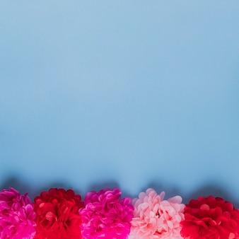 Rij van rode en roze papieren bloem gerangschikt over blauwe oppervlak
