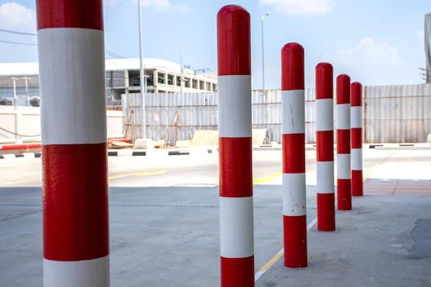 Rij van rode en witte verkeersbarrière paal op parkeerplaats.