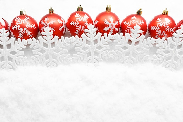 Rij van rode kerstballen met sneeuwvlokken op witte sneeuw achtergrond