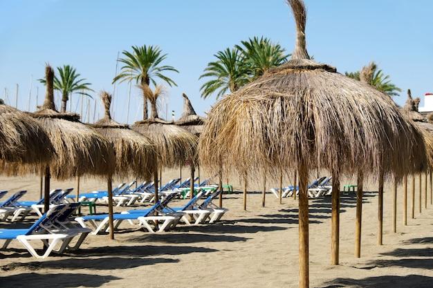 Rij van stro parasols met ligbedden op het strand in marbella, spanje