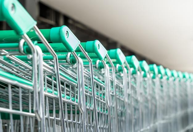 Rij van supermarkt groene emtal winkelwagentje