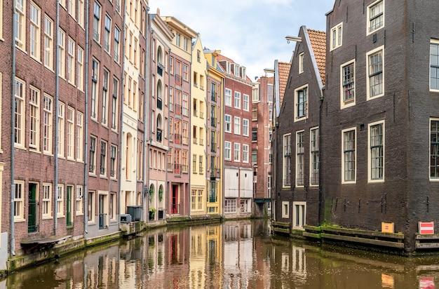 Rij van typische kleurrijke nederlandse huizen weerspiegeld in het water op het amsterdamse kanaal amsterdam nederland