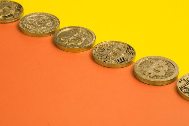 Rij van vele bitcoins over de gele en oranje dubbele achtergrond