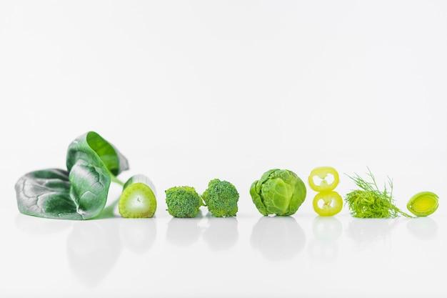 Rij van verse groene groenten op witte achtergrond