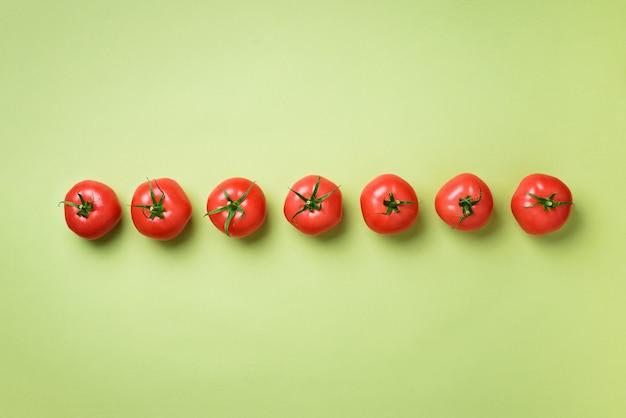 Rij van verse rode tomaten. minimaal ontwerp. vegetarisch, veganistisch, biologisch voedsel en alkalisch maaltijdconcept