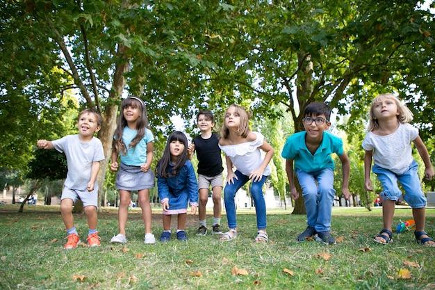 Rij van vrolijke kinderen doen samen squats in park, wegkijken in opwinding. kinderfeestje of entertainment concept