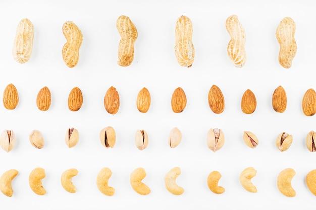 Rij van walnoten; pinda's; amandelen; pistaches en cashewnoten op witte achtergrond