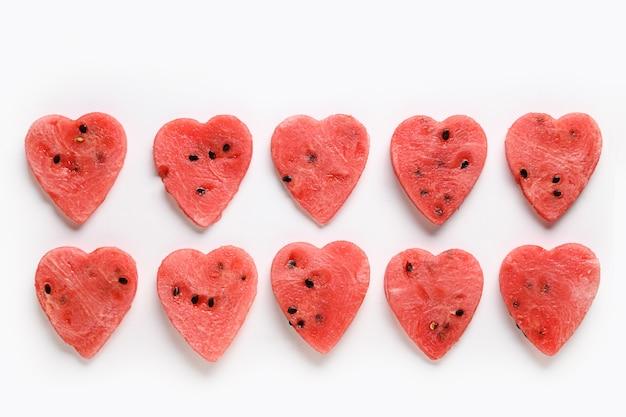Rij van watermeloenplakken als harten op witte achtergrond. plat leggen. voedsel valentijnsdag concept.