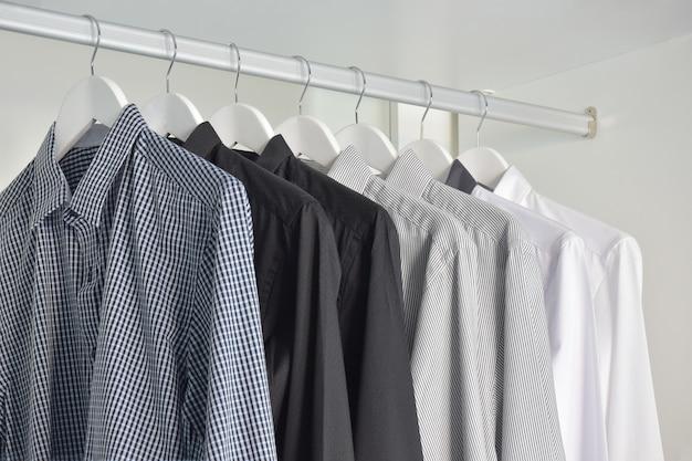 Rij van witte, grijze, zwarte overhemden die in houten garderobe hangen
