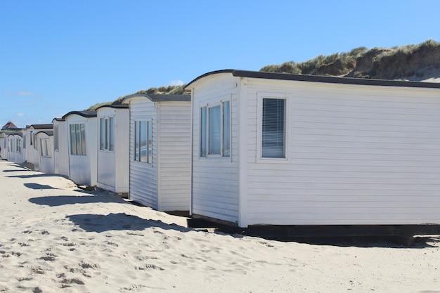 Rij van witte hutten op het strand van lokken, denemarken