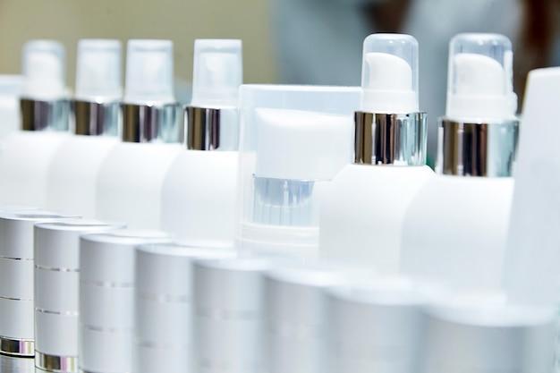 Rij van witte lege flessen met cosmetische producten. hydraterende crèmes. showcase met cosmetica