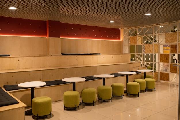 Rij van zachte fluwelen stoelen door witte kleine ronde tafels in het moderne café op de hogeschool of universiteit