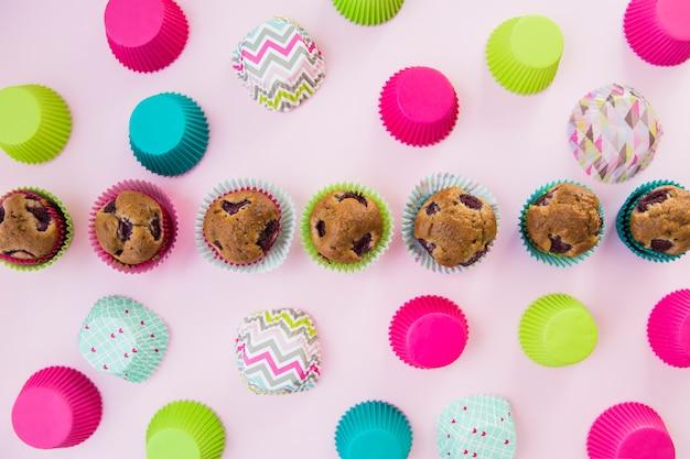 Rij van zelfgemaakte cupcakes omringd met kleurrijke papier houder op roze achtergrond