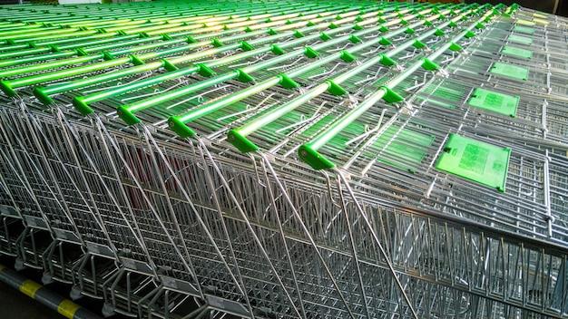 Rij winkelwagentjes met groene handvatten in supermarkt