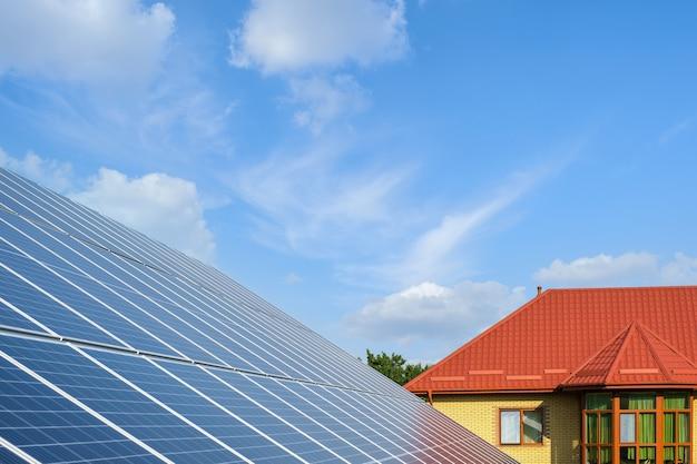 Rij zonnepanelen op een zonneboerderij en huis onder een blauwe lucht