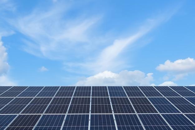 Rij zonnepanelen op een zonneboerderij onder een blauwe lucht