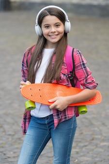 Rijd elke dag. gelukkig kind houdt pennyboard buitenshuis. bord voor vervoer. vrijetijds besteding. actiesport. reizen en avontuur. straat skateboarden. gedreven door skateboard.