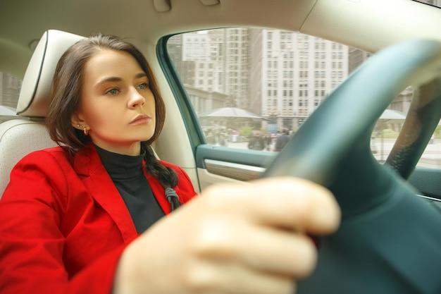 Rijden door de stad. jonge aantrekkelijke vrouw die een auto drijft. jong vrij kaukasisch model in elegante modieuze rode jas die bij modern voertuiginterieur zit. zakenvrouw concept.