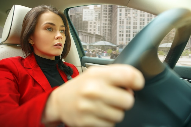 Rijden door de stad. jonge aantrekkelijke vrouw die een auto drijft. jong vrij kaukasisch model in elegante modieuze rode jas die bij modern voertuiginterieur zit