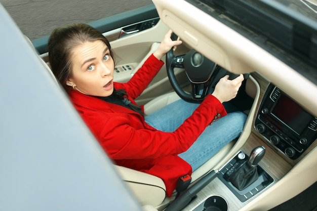 Rijden door de stad. jonge aantrekkelijke vrouw die een auto drijft