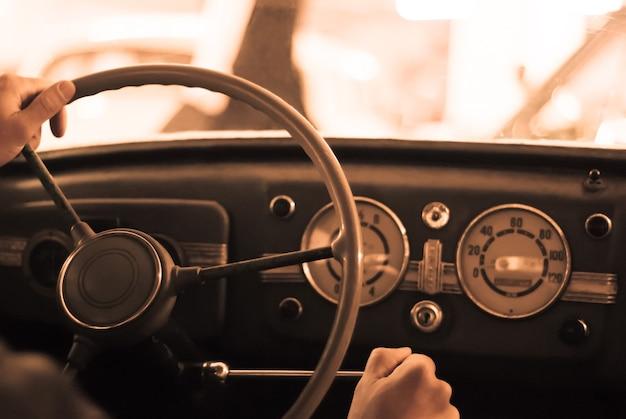 Rijden in een oldtimer; alleen de hand van de bestuurder op het stuur is zichtbaar, het dashboard is wazig; gestileerd als een oude sepia foto met stof en ruis