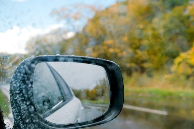 Rijden in regenachtige dag. slecht weer op de weg in herfst- en herfstseizoen. zijspiegel