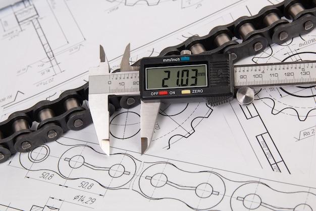 Rijden industriële rollenketting en digitale schuifmaat op een print technische tekeningen