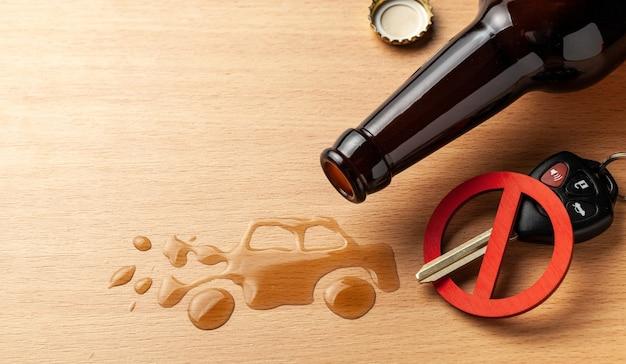 Rijden onder invloed. ongeval met een kapotte auto van alcohol. bierfles en autosleutels. kapotte auto.