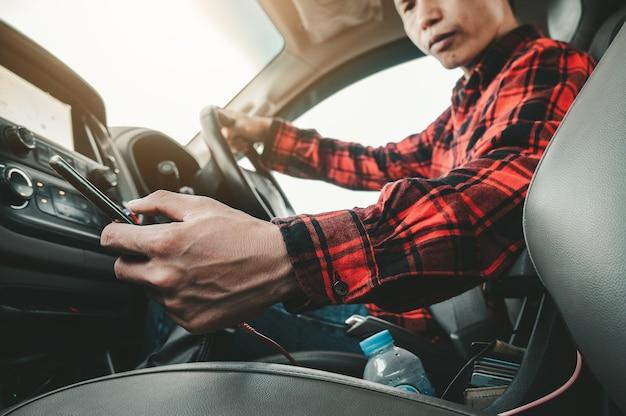 Rijden terwijl hij een mobiele telefoon vasthoudt man kijkt naar mobiele telefoon terwijl hij een auto bestuurt, zijn bocht naar beneden om de smartphone op de auto op te halen. gevaarlijk rijconcept.