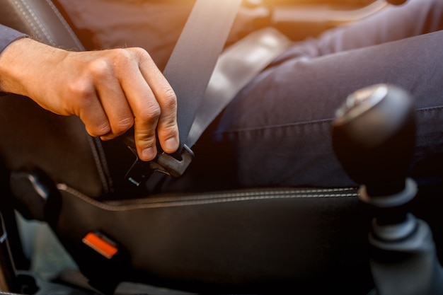 Rijden veiligheidsconcept. een man maakt zijn veiligheidsgordel vast. voordat u gaat rijden